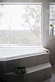 Polygonal bathtub with step in front of panoramic window, gray marbled tiles on the wall and floor
