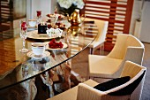Coffee set, tarts and glasses of Champagne on glass table with upholstered chairs