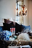 Blue hydrangea flower, glasses of Champagne and bead necklace on tray in bedroom