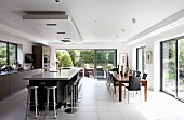 Island counter below suspended ceiling section and spacious dining area in modern, open-plan kitchen