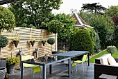 Elegant, grey outdoor tables and neon-green chairs on terrace in front of slatted wooden screen