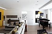 Moderner Wohnraum mit Sofakombination und Klavier vor modernem Bild