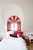 Bed below arched dormer window with semi-circular transom and decorative curtains in shades of red