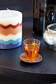 Orange shot glass on wooden saucer next to candle