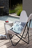 Printed cushion with car motif on white Butterfly chair and stool used as side table on sunny wooden deck next to pool