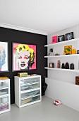 Zimmerecke mit Marilyn-Monroe- Drucken an schwarzer Wand, darunter Schubladenschränke, seitlich Bilder und Objekte auf weissen Wandboards