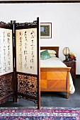 Carved screen with Asian characters in front of an antique bed
