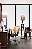 Desk with modern office chair, ethnic floor lamp in front of floor-to-ceiling glazing