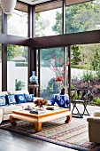Asian light wood coffee table in glazed living room corner with garden view