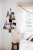 Holzkugelgirlande vor dem Fenster, Fotos in Tannenbaumform arrangiert an der Wand und Klassiker Schreibtischleuchte aus Holz neben Bett