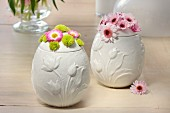 White, egg-shaped china pots decorated for Easter with spring flowers