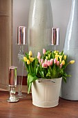 Yellow and pink tulips arranged in pale metal bin and shiny, festive candles on various candlesticks