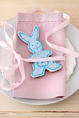 Easter bunny biscuit with pale blue icing on romantic place setting with pink linen napkin