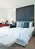 White double bed with tall headboard upholstered in dark grey and white, designer stools at foot