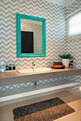 Grey and white, zig-zag wallpaper and mirror with turquoise frame in elegant guest bathroom