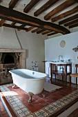 Free-standing bathtub on tiled platform below rustic wood-beamed ceiling