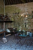 Chairs and tables in room with stone wall and gravel floor
