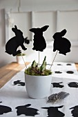 Rabbit-shaped plant pot decorations on Easter table