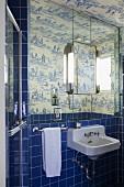 Blue tiles and toile de jouy wallpaper in bathroom