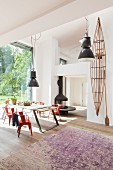 Black pendant lamps in dining area of open-plan interior with gallery and glass wall