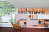 Butterfly armchair in front of shelving in modern interior