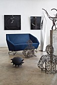 Angular designer sofa surrounded by modern artworks in interior with polished concrete floor