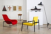 Colourful, designer easy chairs and retro lamp surrounded by artworks in interior with polished concrete floor
