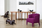 Bronze animals in modern living room with purple armchair and designer console table