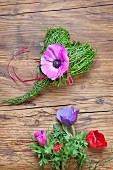 Spring arrangement of bilberry stalks tied into love-heart and purple anemone flowers