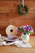 Anemonenstrauss in bäuerlichem Milchkrug und Tellerstapel auf Tisch