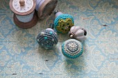 Furniture knobs with crocheted covers on surface with vintage pattern