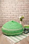 Gehäkelter Sitzpouf in Grün auf grün-weißem Teppichläufer