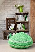 Gehäkelter Sitzpouf in Grün vor Bücherregal aus gestapelten Holzkisten