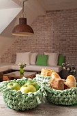 Fruit and bread in green crocheted baskets on wooden table in front of seating area against brick wall