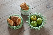 Apples and pastries in crocheted baskets on wooden surface