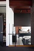 Blick von Vorraum in tieferliegende offene Küche mit schwarz-weißem Farbkonzept