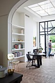 Round table, wire mesh chair, white fitted shelving in open-plan, high-ceilinged interior with traditional, elegant ambiance; man and dog in front of open terrace doors