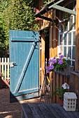 Open wood-shed door and flowering geraniums below lattice window