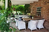 White wicker armchairs and broad table on pleasant wooden terrace between brick façade and climber-covered pergola supports