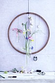 An old wooden hula hoop on a wall decorated with spring flowers