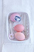 Rosa gefärbte Eier verziert mit Nähfäden in Schälchen