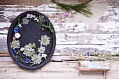 A tray decorated with summer flowers on a wooden surface