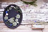 Tablett dekoriert mit Sommerblüten auf Holzuntergrund