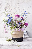 A summer bouquet of cornflowers, vetches, wild carrots and globa amaranth in a vase