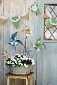 Selbst gebastelte Windräder in Blumentopf und Girlande an Holzhäuschen