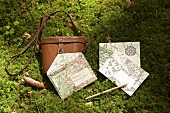 Envelopes made from maps and leather binoculars case on mossy floor