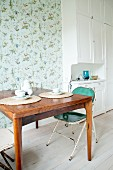 Kitchen table and vintage folding chair in front of bird-patterned wallpaper