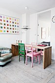 Colourful wooden chairs at minimalist wooden table below classic lamp
