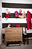 Colourful children's accessories hung from coat pegs and vintage chest of drawers against wall decorated in wide black and white stripes