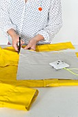 A cushion cover being cut from yellow raincoat material